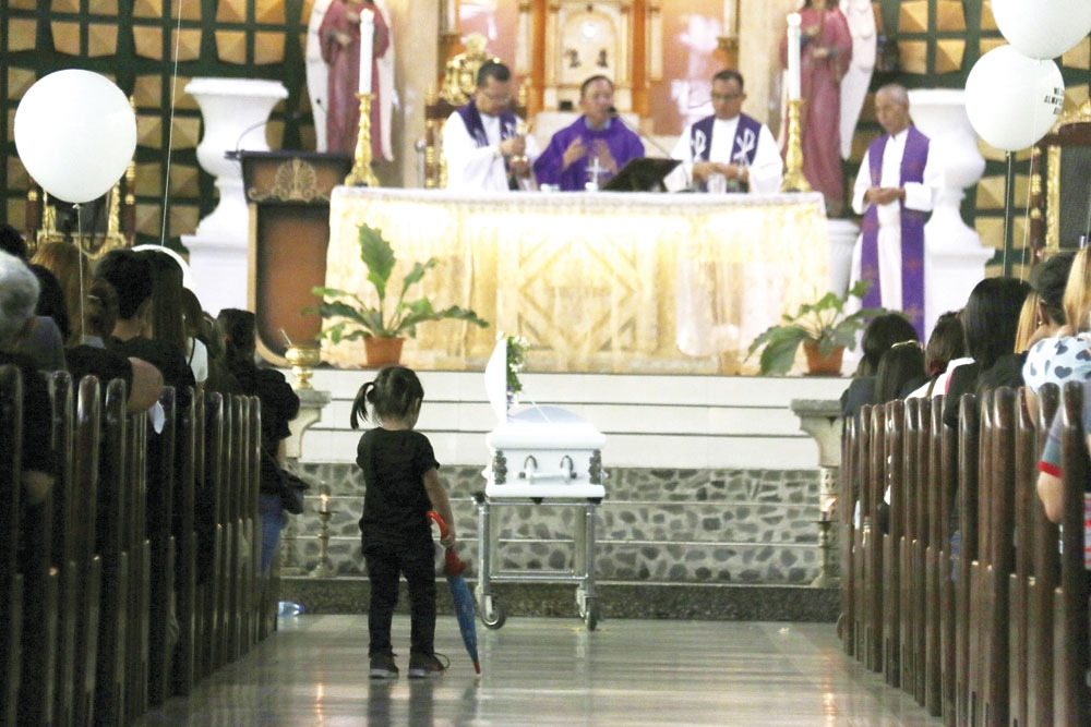 """A box to hold Sky in. A child stands on the aisle of Our Lady of Mt. Carmel-Recoletos during the requiem for Bladen Skyler """"Baby Sky"""" Abatayo, the 4-year-old whom a stray bullet hit in Barangay Ermita, Cebu City during a police operation against suspects linked to illegal drugs. (SunStar Photo/Alex Badayos)"""