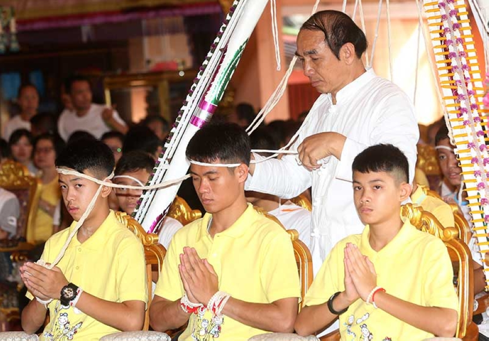 THAILAND. Soccer coach Ekkapol Janthawong, center, and members of the rescued soccer team attend a Buddhist ceremony that is believed to extend the lives of its attendees as well as ridding them of dangers and misfortunes in Mae Sai district, Chiang Rai province, northern Thailand, Thursday, July 19, 2018. The 12 boys and their soccer coach rescued from a cave in northern Thailand left the hospital where they had been recuperating and appeared at a news conference Wednesday, saying the ordeal made them stronger and taught them not to live carelessly. (AP)
