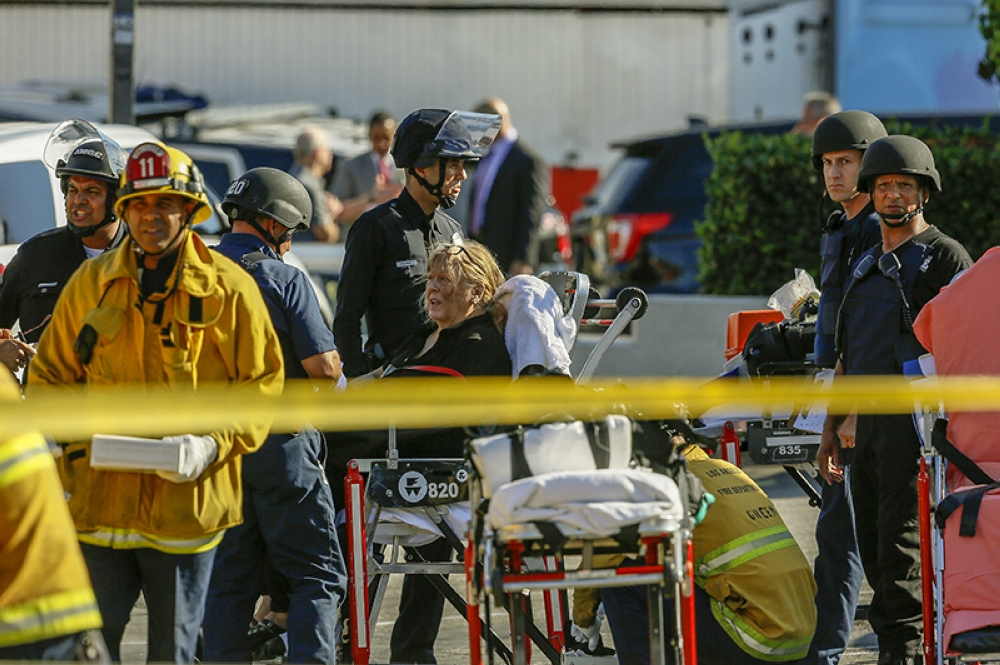 LOS ANGELES. An unidentified woman is helped by paramedics at a triage area after a gunman held dozens of people hostage inside a Trader Joe's store in Los Angeles Saturday, July 21, 2018. Police believe a man involved in a standoff at the Los Angeles supermarket shot his grandmother and girlfriend and then fired at officers during a pursuit before he crashed into a utility pole outside the supermarket and ran inside the store. Hours after he took hostages in the store, the suspect surrendered. (AP)