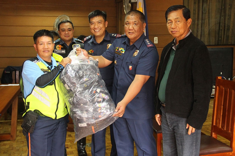 NEW SET OF UNIFORMS. Baguio City Mayor Mauricio Domogan and Baguio City Police Office director Senior Superintendent Ramil Saculles hand over new sets of uniforms donated by the city for the members of the police auxiliary represented by president Elizabeth Widwichan during the VIP Mobile Traffic Assistance and Tactical Convoy Formation Seminar. (Bong Cayabyab)