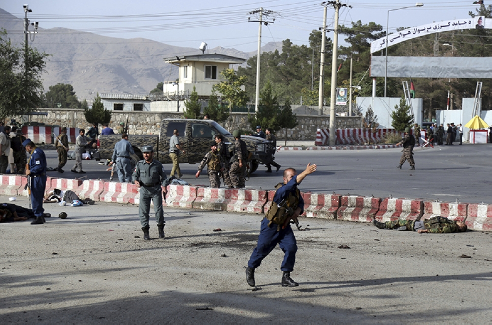 AFGHANISTAN. (Warning, graphic content) An Afghan police officer runs past the bodies of security personal after an attack near the Kabul Airport, in Kabul, Afghanistan, Sunday, July 22, 2018. An Afghan spokesman says there has been a large explosion near the Kabul airport shortly after the country's controversial first vice president landed on his return from abroad. (AP)