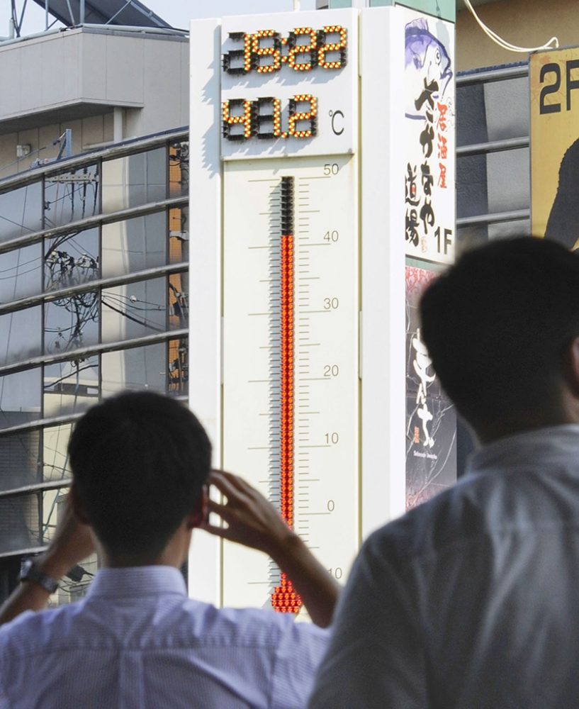 JAPAN. In this July 18, 2018, photo,  people watch the thermometer which reads 41.2 degree Celsius (106.16 degree Fahrenheit) near Tajimi station, Gifu prefecture, central Japan.  (AP)