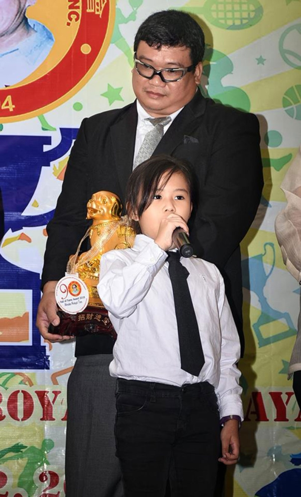 ACCEPTANCE SPEECH. Hall of famer Atsuko Kaiyel Tan delivers her speech while her father Rommel holds her award during the 24th So Kim Cheng (SKC) Awards Night held at the Royal Ballroom of The Royal Mandaya Hotel Sunday evening. (Dabaw City Sports Council Inc. photo)