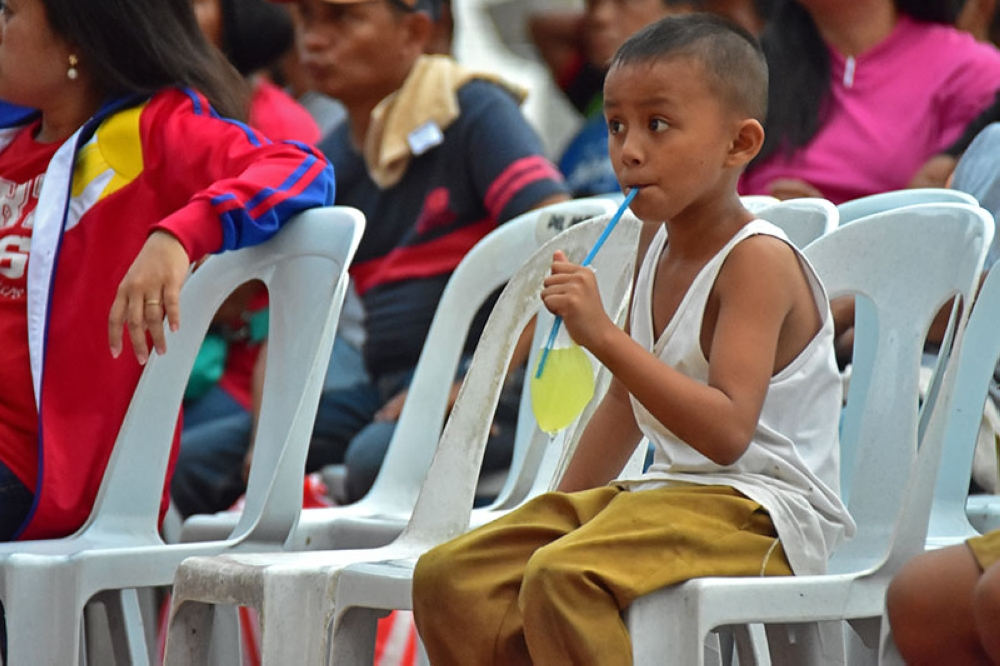 DAVAO. A boy sips his soda as he listens to the State of the Nation address seated in front of the crowd Monday, July 23, at Rizal Park in Davao City along with 500 other Dabawenyos who converged in the area to listen to President Rodrigo's report to the nation. (Photo by Macky Lim)