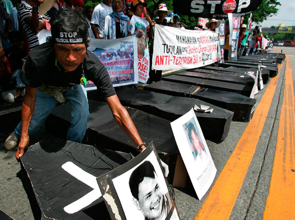 MANILA. In this June 10, 2006, file photo, a man arranges mock coffins symbolizing the number of their companions killed or abducted, allegedly by the military, at a rally marking the 18th anniversary of government land reform in Quezon City, Philippines. (AP)