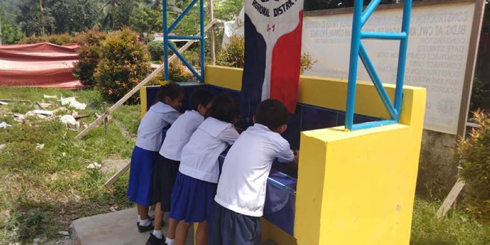 UAP North Davao President Galio Palmera teaches school children the proper use of the handwashing facility. (Contributed photo)