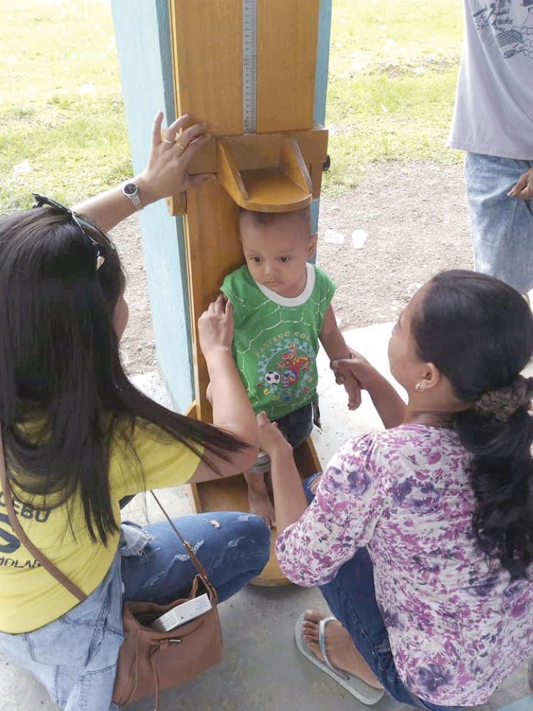 Scorecard. A toddler's height is taken as part of the National Nutrition Council's Early Childhood Care and Development Intervention Package for the First 1,000 Days program in Tuburan, Cebu. The Provincial Health Office's Our Cebu Program Scorecard 2018 will rate local government units on how well they reduce the prevalence of malnutrition in their areas. (National Nutrition Council 7 Foto)
