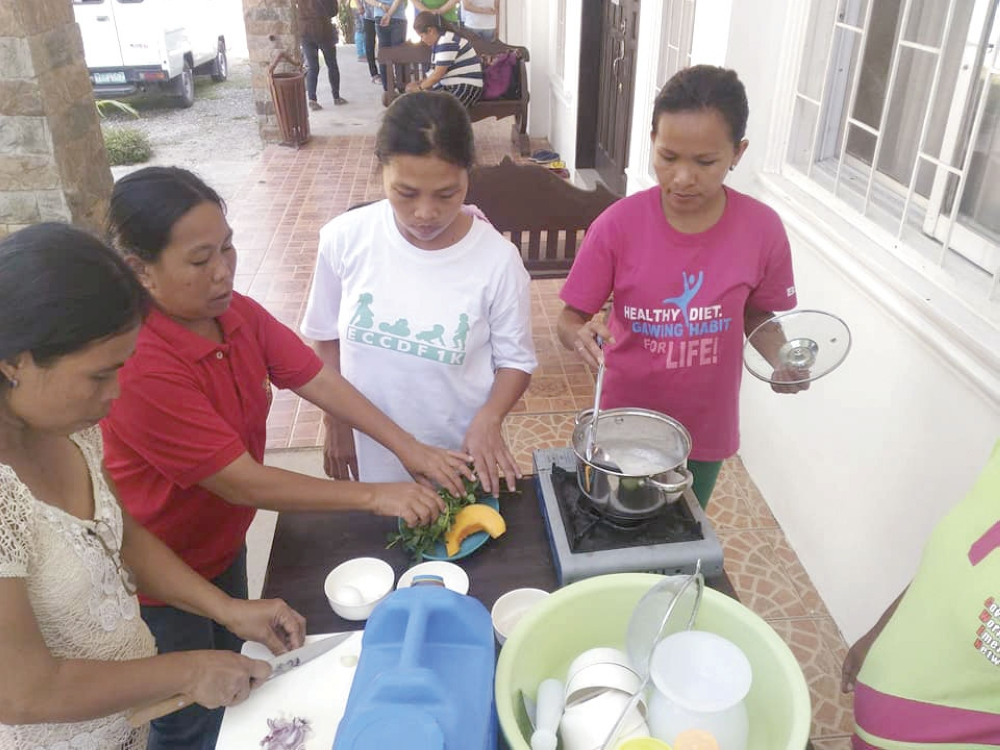 Cooking demo. Mothers learn how to prepare complementary food appropriate for their children during this cooking demonstration conducted in Tuburan. (National Nutrition Council 7 foto)
