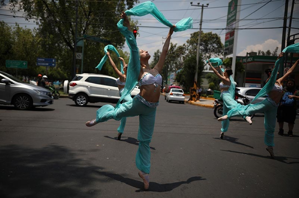MEXICO. Ballerinas dance in the middle of a street during a red traffic light in Mexico City, Saturday, July 28, 2018. In this sprawling megalopolis notorious for its clogged streets, a theater company sent out tutu-clad dancers out to delight motorists at snarled intersections with snippets from ballet classics like The Nutcracker and Swan Lake all in the 58 seconds it takes for the light to go from red to green. (AP Photo)