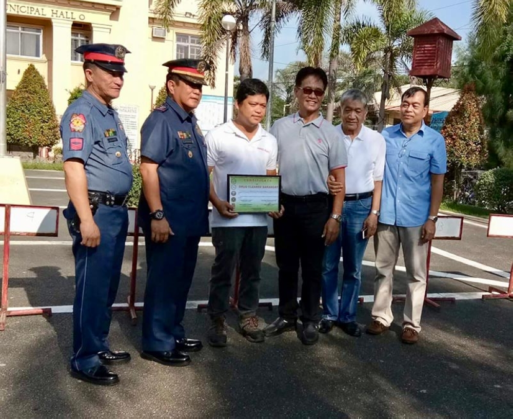 """PAMPANGA. Lubao Municipal Police Station officer-in-charge, Police Supt. Angelito B. Esteban (2nd from left), and SPO3 Rodolfo Bacani Jr. (left) present to Councilor  James Maris the certificate declaring Barangay Sta. Tereza I as """"drug-cleared.""""  Witnessing the awarding of certificate are municipal councilors Emmanuel Santos and Gonzalo Tungul and Municipal Administrator Elizalde Bernal. (Photo Courtesy of Sarah Skyler Mallari Bucu)"""