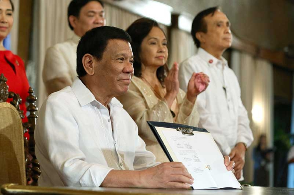 MANILA. President Rodrigo R. Duterte shows a copy of the Philippine Identification System (PhilSys) Act after signing it during a ceremony at Malacañan Palace on August 6, 2018. (Presidential Photo)