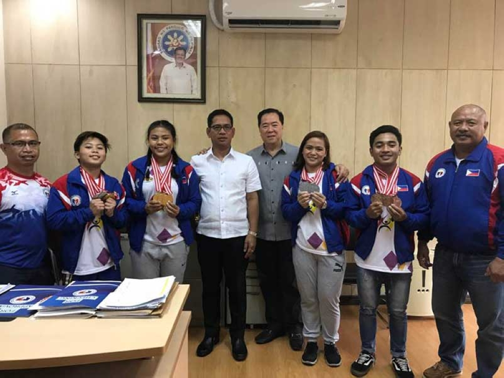 Pinoy weightlifting medalists share their medals withSamahang Weightlifting ng Pilipinas president Monico Puentevella (center). (Contributed Photo)