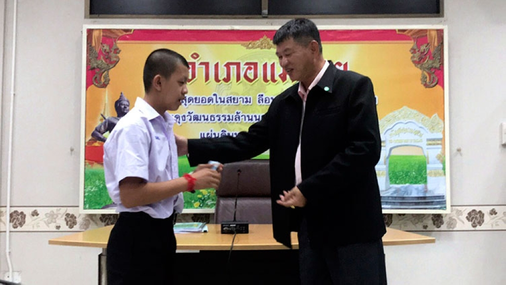 THAILAND. In this release by Chiang Rai Public Relations Office, Pornchai Kamluang (left) receives an identity card denoting Thai citizenship from Somsak Kunkam Sheriff of Mae Sai during a ceremony in Mae Sai district, Chiang Rai province, northern Thailand, Wednesday, August 8, 2018.(AP)
