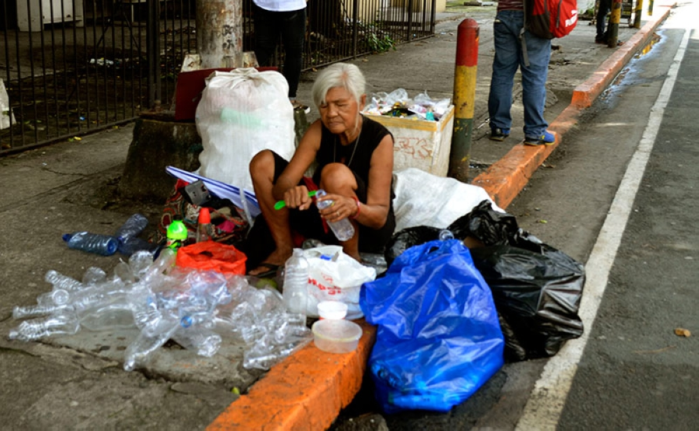 MANILA. In this photo taken on July 25, 2018, an old lady earns a living by cleaning plastic bottles for recycling on a sidewalk in Ermita, Manila. (Alfonso Padilla/SunStar Philippines)