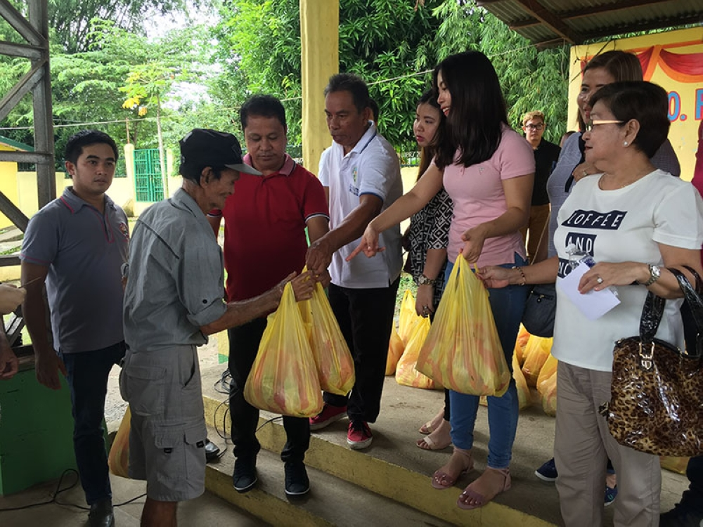 PAMPANGA. GlobalCrete Inc. owner Rene Maglanque hands over relief packs to flood victims in Barangay Sto. Rosario. Joining him are Vice Mayor Michael Sagum, and Councilors Charina Sombillo, Maine Santiago and Linda Salac. (Photo by Princess Clea Arcellaz)