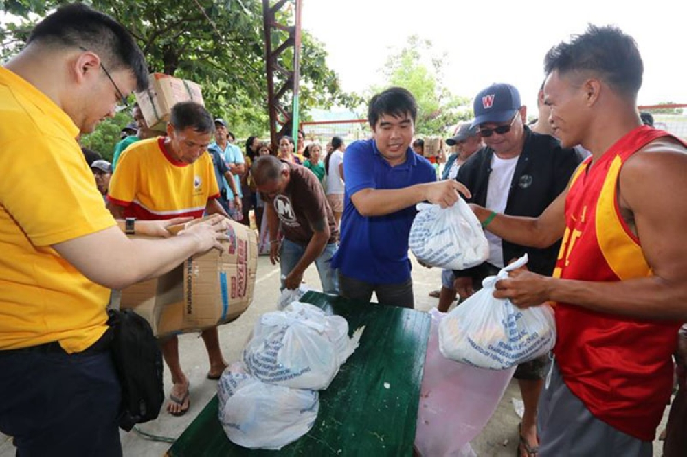 PAMPANGA. Masantol Vice-Mayor Ralph Nulud and San Fernando Pampanga Filipino Chinese Chamber of Commerce and Industry Inc. director Mark Chua hand over on August 7 relief goods to some 2,300 flood victims in Masantol town. (Photo by Chris Navarro)