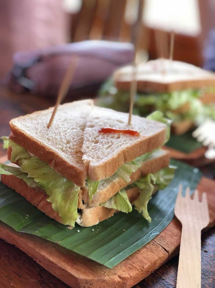 BUKIDNON. Tuna sandwich served on a wooden board, banana leaves, and wooden fork. (Hannah Victoria Wabe)