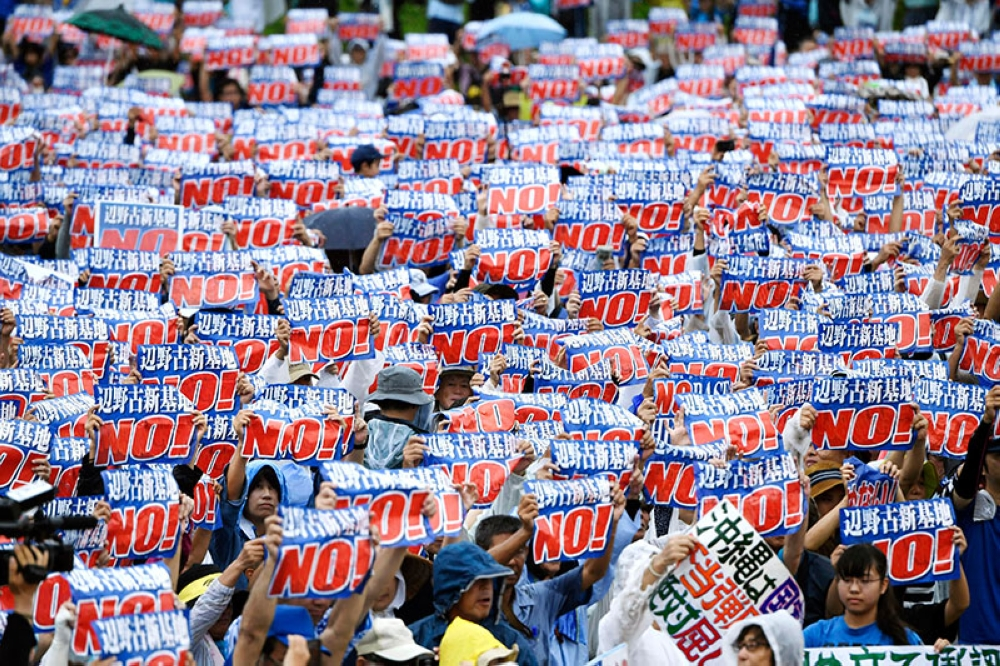 TOKYO. Protesters display signs against a planned U.S military base relocation during a rally in Naha, Okinawa prefecture, on the southern Japanese island Saturday, Aug. 11, 2018. (Kyodo News via AP)