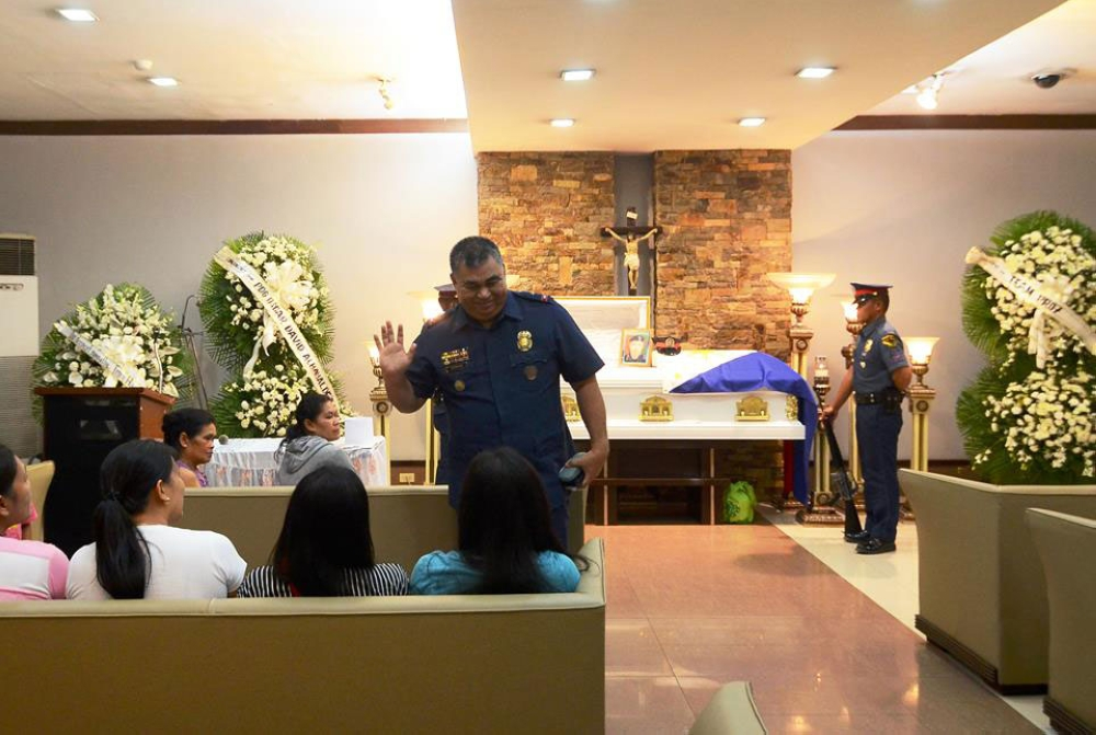"Miduaw. Si Police Regional Director Debold Sinas (gakaway sa kamot) usa sa mga nag-una og duaw sa haya ni SPO1 Roderick Balili niadtong Sabado sa St. Peter's Chapel sa Imus Road, Cebu City. Si Sinas ang nikompirmar sa pagkaangol ni Balili sa iyang giingon nga ""accidental firing"" nga wa tuohi ni Cebu City Mayor Tomas Osmeña. (Alan Tangcawan)"