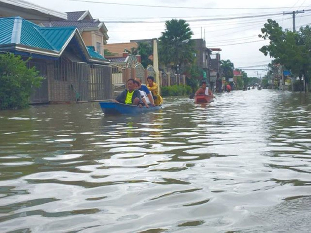 PAMPANGA. The Barangay Caduang Tete portion of Apalit-Macabebe-Masantol road has become a river where bancas are now the only mode of transportation in the area. (Princess Clea Arcellaz)