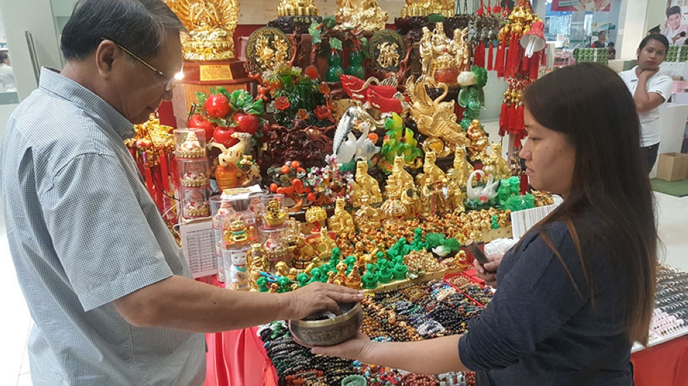 CLEANSING BOWL. Let Let Lomugdang (right) performs a ritual for a customer who just bought a charm from her stall in Parkmall. Lomugdang says the Ghost Month is a time for businesses to be cautious about making big decisions. (SunStar photo /  Ruel Rosello)