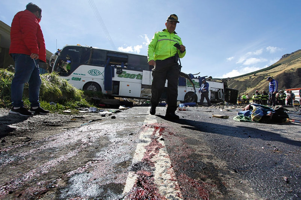 ECUADOR. A police officer walks past a Colombian-registered bus traveling to Quito that crashed in Pifo, Ecuador, Tuesday, Aug. 14, 2018. (AP)