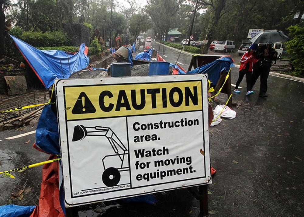 BAGUIO.  Pedestrians pass the construction area along Burnham Park lake drive with caution amid strong rain in Baguio City. (Photo by Jean Cortes)