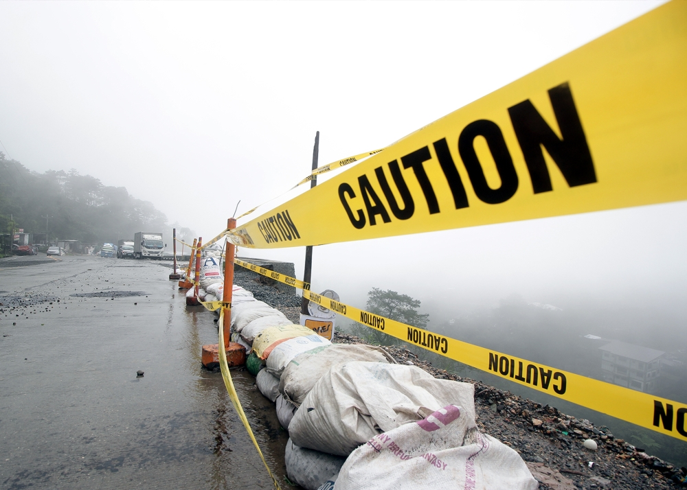 BAGUIO. A caution sign was put up along the foggy and newly widened Marcos Highway to warn motorists of landslides. (Photo by Jean Cortes)