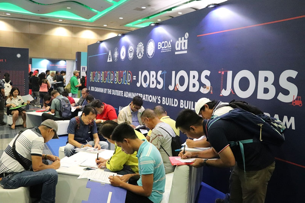PAMPANGA. Job hunters fill up application forms during the Jobs Jobs Jobs Caravan last Sunday in Pasay City. (Contributed photo)