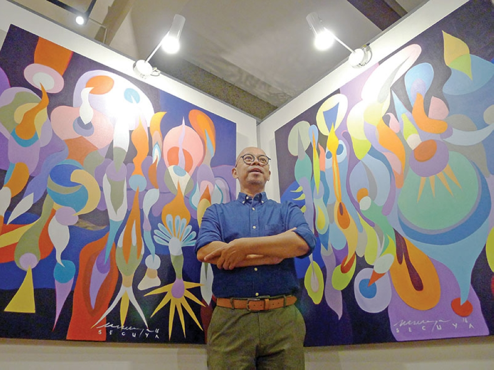 DAVAO. Victor 'Vic' Secuya gives a preview of thepaintings at he will exhibit in Belgium. (Photo by Jinggoy I. Salvador)