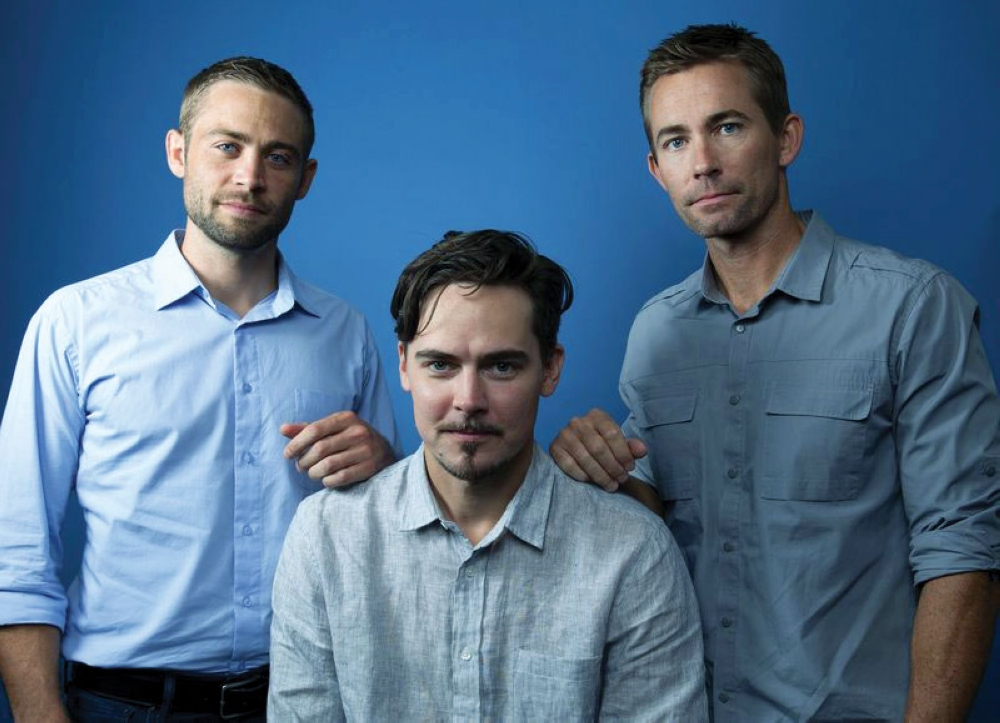 """'I am Paul Walker.' Brothers Cody (left) and Caleb Walker (right) pose with Adrian Buitenhuis, who directed the documentary film """"I Am Paul Walker."""" The film is a one-hour documentary about the actor's childhood, family and career. It premiered last weekend on the Paramount Network. (AP Foto / Rebecca Bage)"""