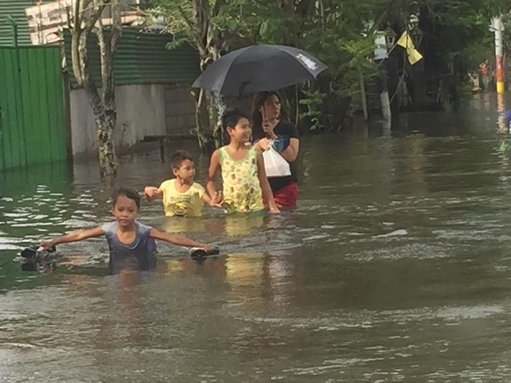 A boy has fun wading in floodwaters ahead of a mother and her children in Barangay Caduang Tete, Macabebe town. (Photo by Princess Clea Arcellaz)