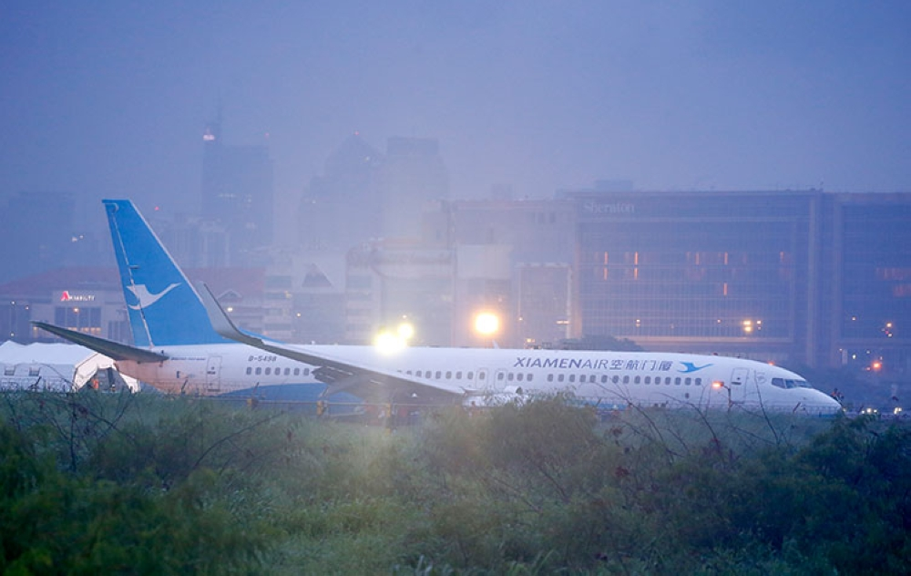 MANILA. Rescuers are seen at the scene as a Boeing passenger plane from China, a Xiamen Air, lies on the grassy portion of the runway of the Ninoy Aquino International Airport after it skidded off the runway while landing Friday, August 17, 2018 in Pasay City. (AP)