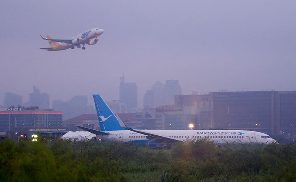 MANILA. A Cebu Pacific passenger plane takes off, in background, while a Boeing passenger plane from China, a Xiamen Air, lies on the grassy portion of the runway of the Ninoy Aquino International Airport after it skidded off the runway while landing Friday, August 17, 2018, in Pasay City. (AP)