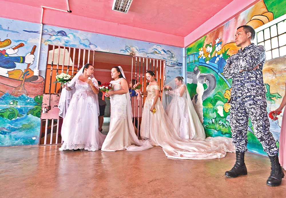 Now, that's commit-ment. A jail officer (right) stands guard as some brides prepare for a mass wedding inside the Cebu City Jail. (SunStar Foto / Amper Campaña)