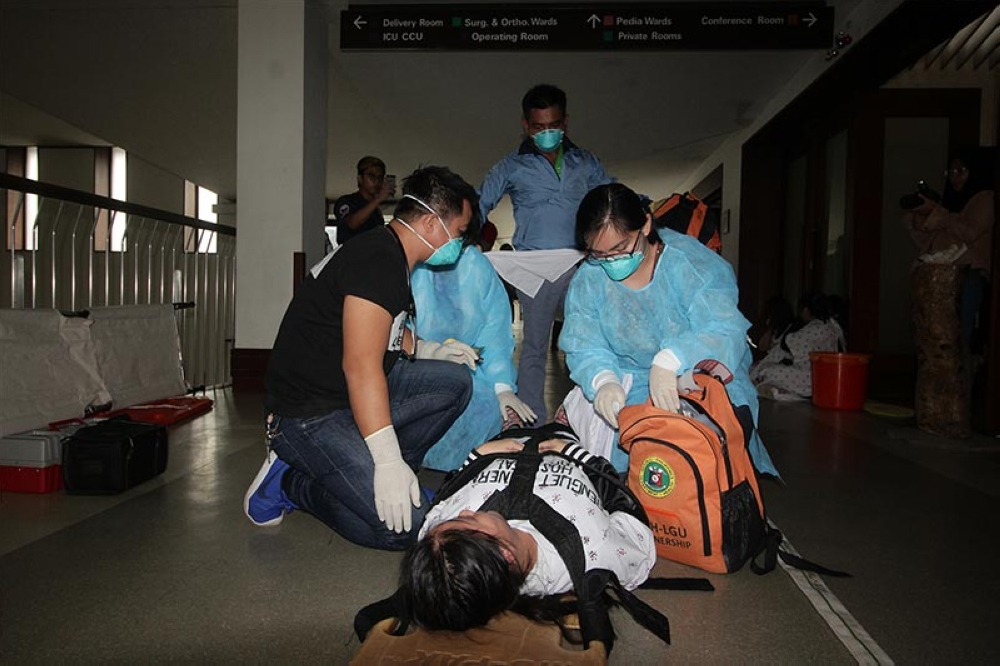 DRILL. Rescue workers rush to a supposed victim during the 3rd Quarter Nationwide Earthquake Drill at the Benguet General Hospital. (Jean Cortes)