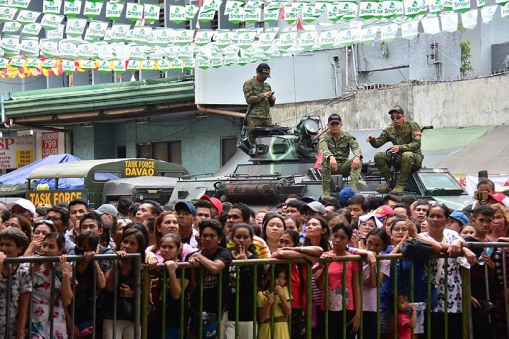 BANTAY. Mga sakop sa Task Force Davao mitungtong sa ilang tanke-de-gira aron makita ang palibot samtang nagpunsisok ang mga tawo nga nanan-aw sa mga nindot nga floats sa Pamulak sa Kadayawan sa San Pedro Square, Davao City, kagahapon. (Macky Lim)