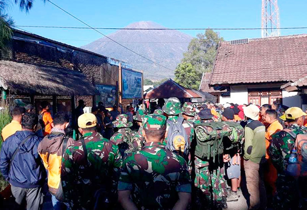 INDONESIA. In this July 30, 2018, file photo, Indonesian soldiers and rescue team gather to prepare for evacuating tourists from Mount Rinjani, seen in the background, at Sembalun in East Lombok, Indonesia. (AP)