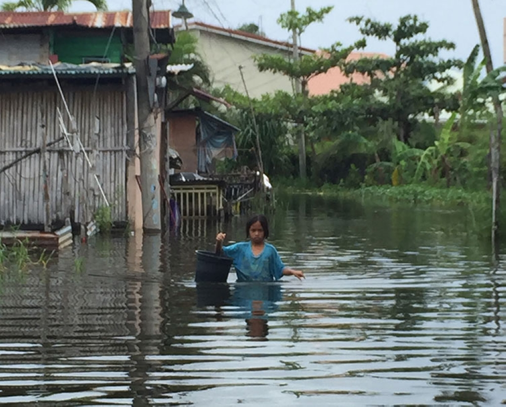 PAMPANGA. A young girl braves floodwaters to sell the prawns placed in a pail her father harvested from an overflowed fishpond in Masantol, Pampanga. (Princess Clea Arcellaz)