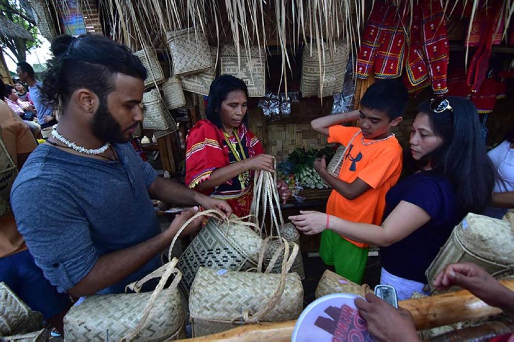 DAVAO. Mga bisita sa Kadayawan village nagpalit og bag nga ginama sa kamot sa Matigsalug didto sa Magsaysay Park sa siyudad sa Davao atol sa kasaulogan sa Kadayawan. (Macky Lim)