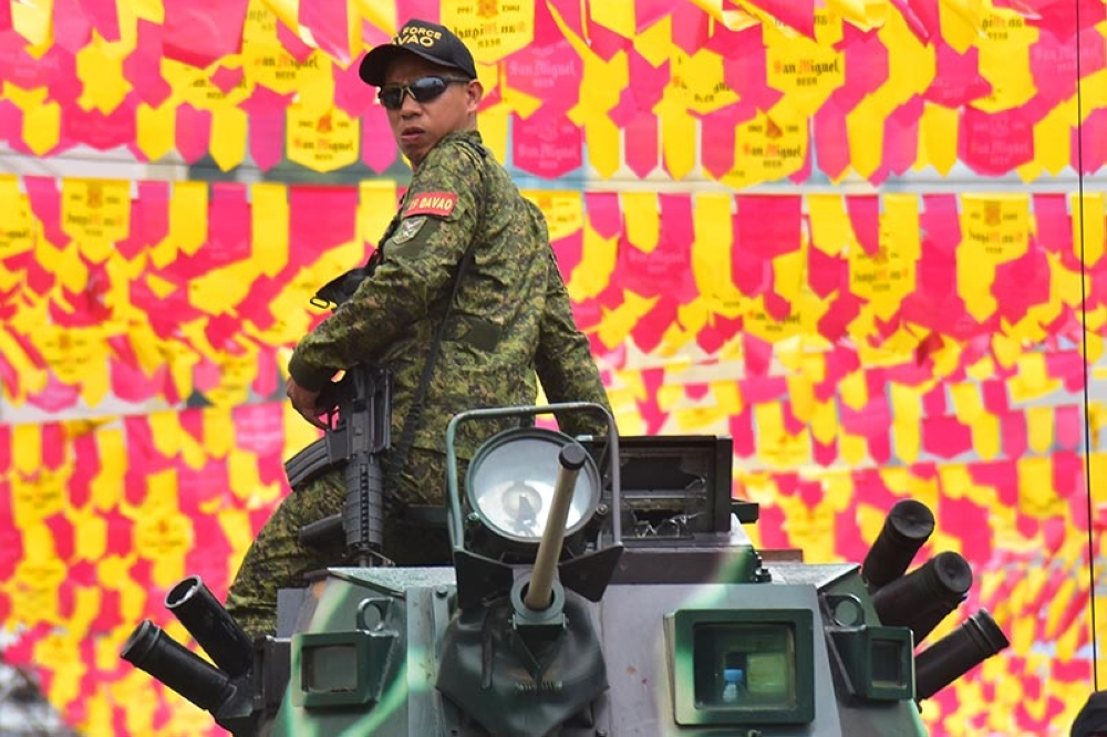 DAVAO. A Task Force Davao personnel onboard an Armored Personnel Carrier keeps an eye on the crowd during the Pamulak sa Kadayawan Parade on Sunday, August 19. (Photo by Macky Lim)