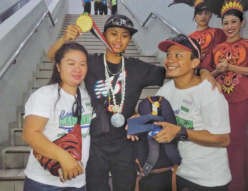 LIFE TAKES A FULL TURN. Asian Games gold medalist Margielyn Didal is welcomed by her parents Julie and Lito Didal and her friends from Barangay Lahug. (SunStar Photo/Allan Cuizon)