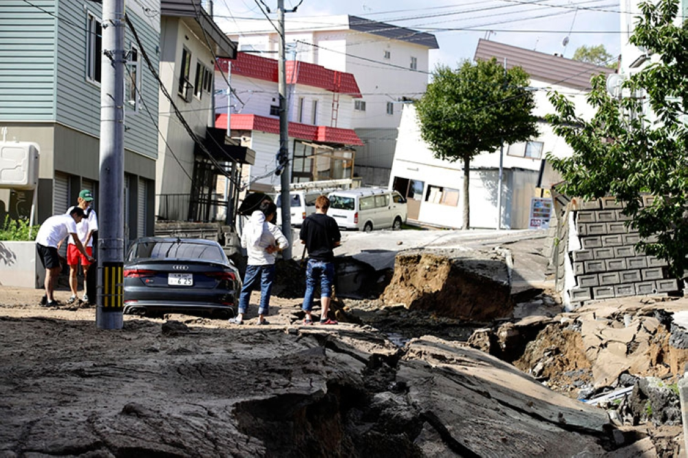 JAPAN. Residents watch a road damaged by an earthquake in Sapporo, Hokkaido, northern Japan, Thursday, September 6, 2018. (AP)