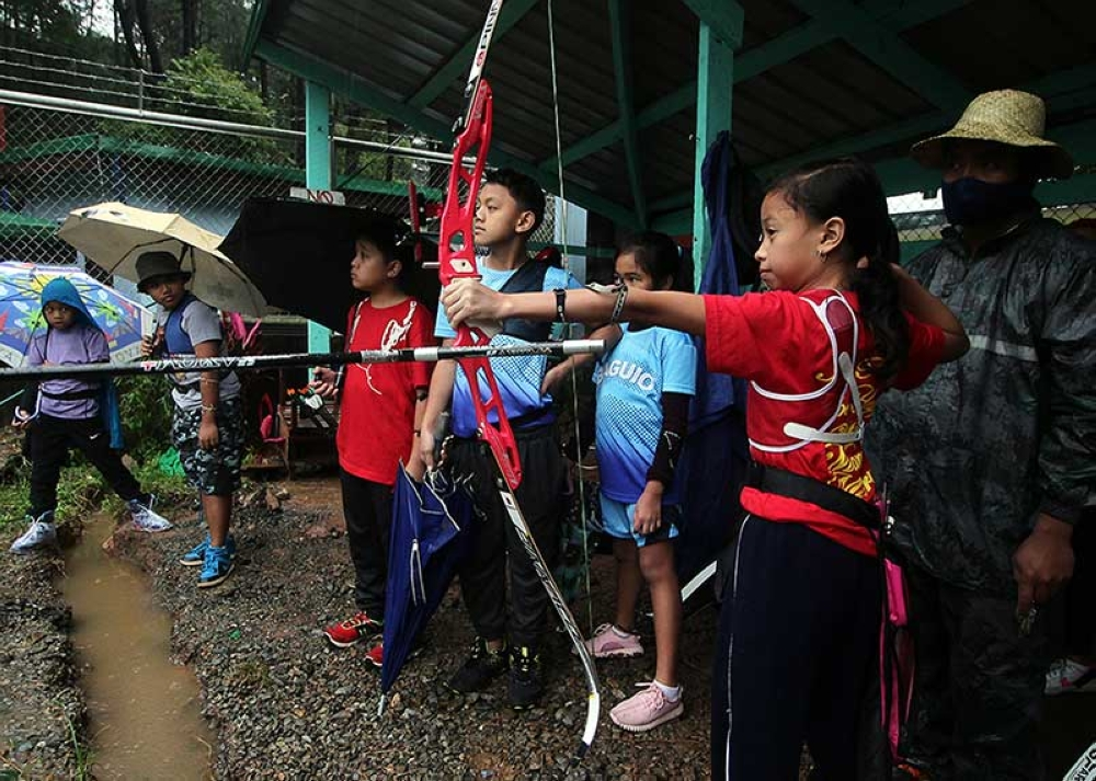 BAGUIO. Rain or shine, young archers from the Summer Capital push through with their training in a bid to secure medals in the upcoming Batang Pinoy national finals. (Photo by Jean Nicole Cortes)