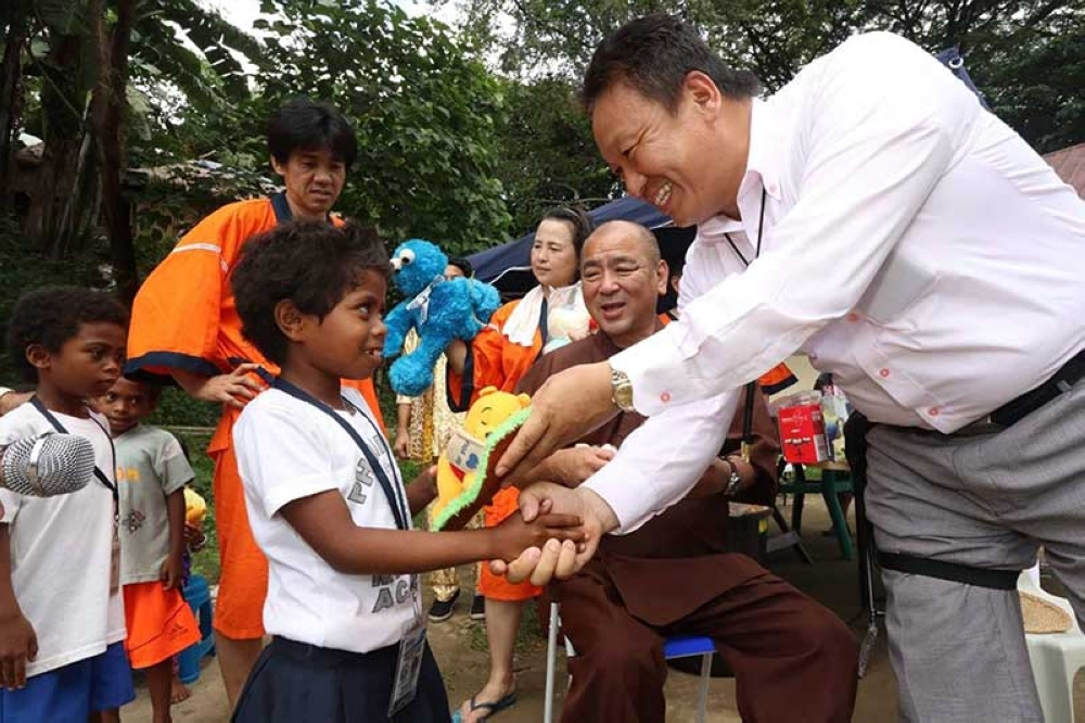 PAMPANGA. Izumisano City Councilor Hidetaka Nakashouya (right), Buddhist monk and Shinto priest Shinkou Iwahashi (center) and MUSUBI representative director Takatsuga Yamada (left), led Monday's distribution of toys, notebooks, clothing and shoes to some 400 Aeta students at Camias High School and Camias Resettlement Elementary School in Porac, Pampanga. (Photo by Chris Navarro)