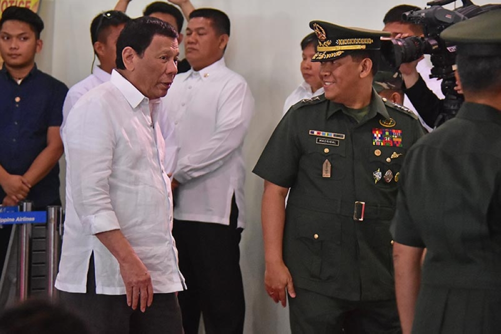 DAVAO. President Rodrigo Duterte accompanied by Eastern Mindanao Command Commander Lt. Gen Benjamin Madrigal during the arrival honors at the Davao International Airport Saturday after his official state visit in Israel and Jordan. The President in his speech said that Coup d'état does not appeal to him at all and is unfazed with the plans to kick him out of the presidency. (Macky Lim)