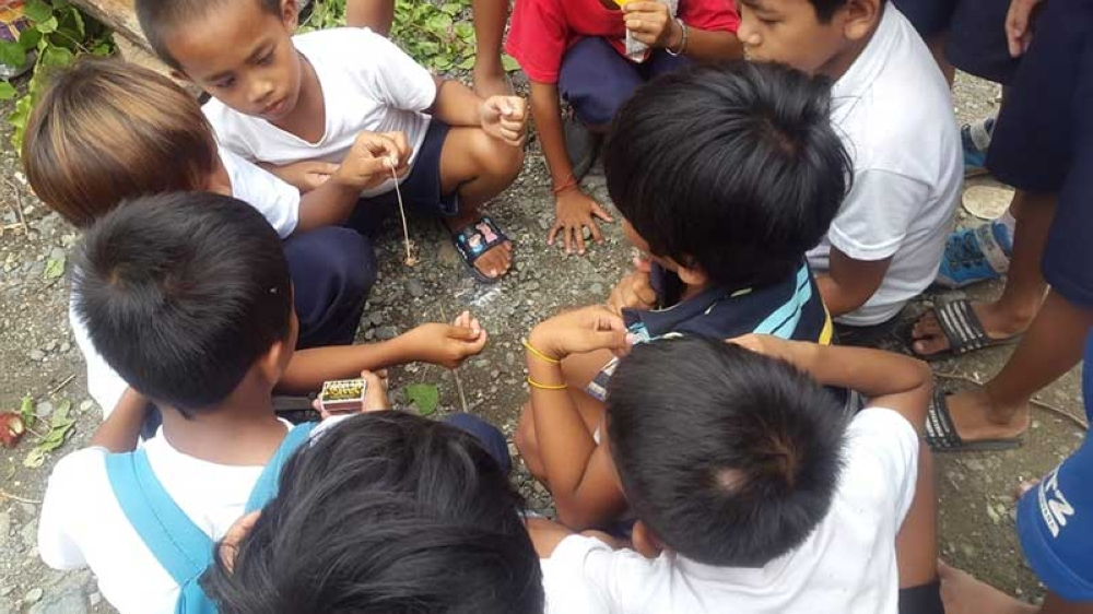 CAGAYAN DE ORO. School children playing with spiders being sold in some school premises of Cagayan de Oro especially during the onset of rainy season. (Lynde Salgados)