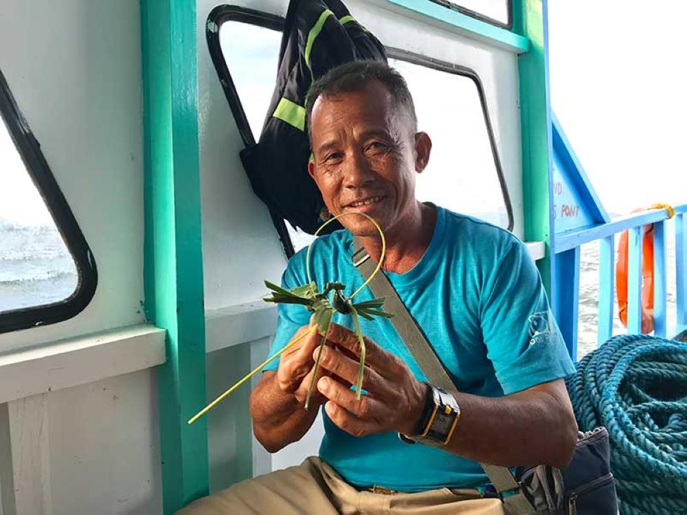 Boat crew Roquero Enrile weaving coconut leaves. (Stella A. Estremera)