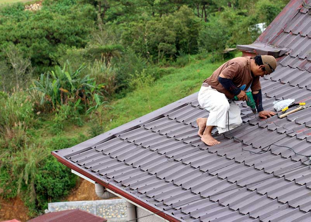 BENGUET. A homeowner in Tuba, Benguet repairs his roof as a pre-emptive measure ahead of Typhoon Ompong. (Photo by Jean Nicole Cortes)