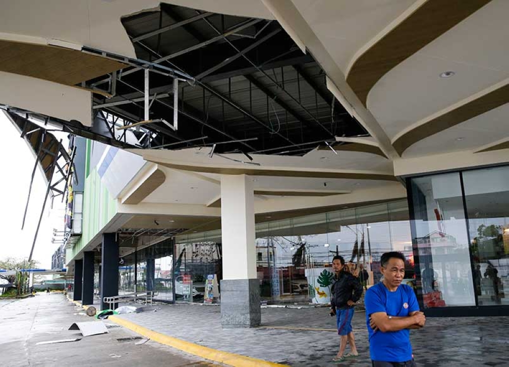 TUGUEGARAO. Residents stand beside a damaged portion of a mall due to strong winds from Typhoon Mangkhut as it barreled across Tuguegarao city in Cagayan province, Saturday, September 15. (AP)